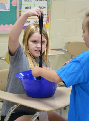 In the Slime Time class, Ella Wheeler, 8, stretches out a glob of magnetic slime that she and her partner, Emilee Vanoy, 9, had just created.