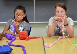 Nataliine Martinez, left, and Hailey Murlock practice the art of finger knitting during a sewing class.