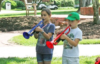 Kendra Peek/kendra.peek@amnews.com Anna, 9, left, and Max Watson, 7, right, play trumpets at the Creation Station in the Great American Brass Band Festival.