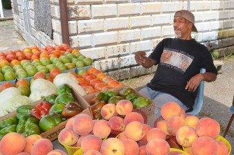 Terry Doneghy sits behind his produce stand on South Second Street Tuesday afternoon.
