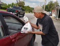 Terry Doneghy takes a bag of green peppers out to his aunt when she stopped by Tuesday afternoon.