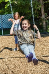 Ben Kleppinger/ben.kleppinger@amnews.com Diana Corona-Hernandez, front, gets a push from Stella Feistritzer on one of the playground's new swings.