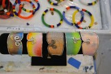 Watercolor paper bracelets wrapped in silver wire and coated with acryilic are some of the jewelry that Woodward and her granddaughter, Grace McDaniel, are creating. The South African glass beaded bracelets that she's selling for her friend Dlalie are in the background.