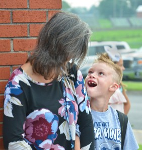Brayson Cochran looks up to his mom, Michelle Cochran as they wait for the doors to open allowing parents to walk into Woodlawn with their children on the first day of school. Brayson was entering indergarten.