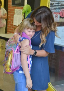 Sophia Bryant, a first-grader at Woodlawn this year, is hugged by kindergarten teacher, Ashley Anderson on the first day of school.
