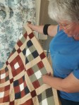 Janie Taylor indicates a signature square on a quilt