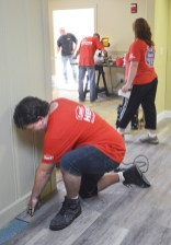 Photo by Robin Hart/robin.hart@amnews.com Jacob Betler, from Danville Lowe's store, lays down flooring in the Gibson Cottage, as other Lowe's Heroes work in the background.