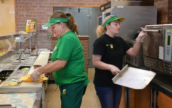 Jeannie Brewer, left works on a customer's wrap sandwich as co-worker LeeAnn Confer starts to take another customer's order from the oven at the Subway on Fourth Street in Danville.