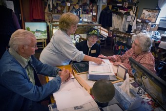 Photos by James Morris Pat McDaniel of Greenwood, Indiana, looks through genealogy records with community center museum volunteers Monty Bryant, Shirley Sheperson and Carolyn Crabtree. McDaniel was searching for records of her ancestors who lived in Forkland.
