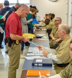 Ben Kleppinger/ben.kleppinger@amnews.com Participants interact with inmates during the simulation, attempting to pass urinalysis tests, obtain food, cash checks and receive driver's licenses, among other tasks.