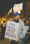 Photo by Robin Hart/robin.hart@amnews.com Bob Fieberg holds a sign during Thursday night's local protest which was part of a nationwide protest.