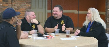 Photo by Robin Hart/robin.hart@amnews.com Chad Holderman, center, shares a laugh with Danny Sallee, left and Melissa Jones, right, during the first responders' appreciation lunch on Thursday.
