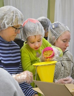 Robin Hart/robin.hart@amnews.com From left, Lori Brunner watches Anna Kerri Cundiff as she carefully pours dried pasta into a funnel as Laikyn Francis gets another cup of pasta ready to pour.