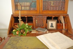 A simple arrangement of magnolia leaves and apples surrounds a candlestick on the desk in the upstairs hall. Materials used to decorate would have been available in the early 19 th century when the McDowell family lived in the house. (Photo by Andrea Perkins)