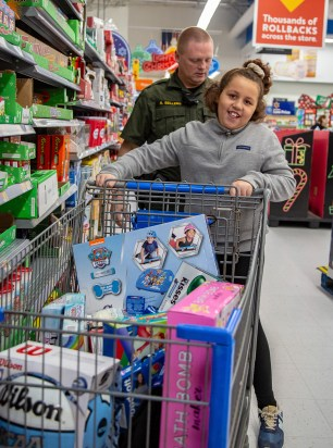 Ben Kleppinger/ben.kleppinger@amnews.com Maddison, an 8-yearold Junction City Elementary School student, commandeers her shopping cart as Boyle County Deputy Ricky Sellers adds up prices on a calculator app.