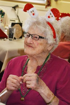 Photo by Robin Hart/robin.hart@amnews.com Betty Murphy, a resident at McDowell Place of Danville, is dresssed for Christmas by wearing a Santa headband and jinglebell necklace at the combined performance of KSD's Signing Choir and DHS's American Sign Language classes Tuesday.
