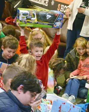 Photo by Robin Hart/robin.hart@amnews.com Kentucky School for the Deaf student Toby Mills excitedly lifts his new remote-control truck after opening the gift from the Brothers Code Motorcycle Club from Danville.