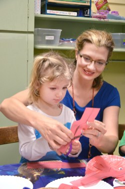 Alleena Van Horn teaches her daughter Emery how to cut paper using safety scissors. Photo by Robin Hart. Photo by Robin Hart.