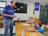 David Morris is signed into Junction City Elementary School's leadership luncheon by Lighthouse team members Abigail Piscatelli and Jansen Barnes. Photo by Robin Hart.
