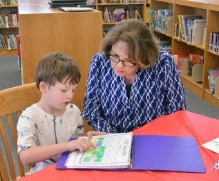 Cyrus Tipton explains how he keeps track of his behavior on charts as part of the school's Leadership in Me program to Pam Tamme. Photo by Robin Hart.