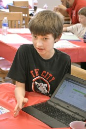 Logan Ball uses a laptop to keep a record of his school accomplishments for the Leadership in Me program at JCES. Ball was explaining how the program works to several adults who were treated to a luncheon at the school to learn more about the Leadership in Me program. Photo by Robin Hart.