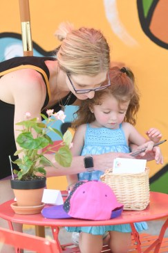 Amber and Hadley Phillips fill out the sign in sheet at the pop up park on Saturday.(Photo by John Scarpa)