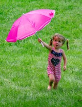 Danville resident Hadley Phillips, 2, holds her parasol up while playing on the Centre College lawn Saturday afternoon, shortly after Brass Band Festival organizers announced incoming storms would force the rest of the day's concerts and events inside. (Photo by Ben Kleppinger)
