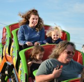 Danielle Arvin and her daughter Bayleigh Smith enjoy a thrill on the small roller coaster at the Boyle County Fair Tuesday evening. (Photo by Robin Hart)