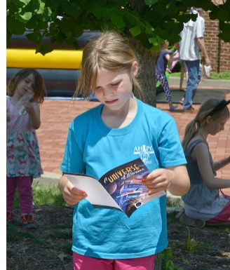 Brigid Kelly, 8, of Danville, looks through a reading guide that was in a bookbag she received during the Boyle County Public Library summer reading program kick off event on Monday. (Photo by Robin Hart)