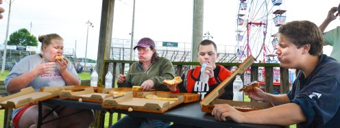 From left, Keyla Peach, of Harrodsburg, Stacey Carter and Nick Rigney, both of London, and Lincoln Lutz were the only competitors in the pizza eating contest Wednesday evening. Peach won $10 by eating the most pizza within two minutes. (Photo by Robin Hart)