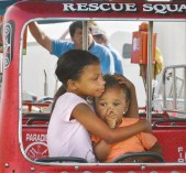 Nasir Penix,7, holds her brother Makey, 2, on a kiddie ride at the fair Tuesday evening.