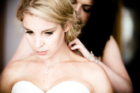 bride looking down and havinf the hairdresser behind