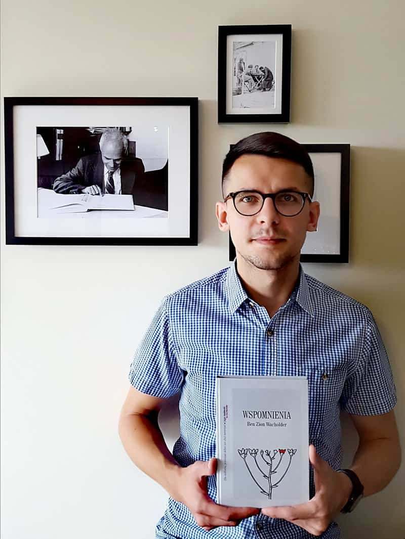 Lukasz Rzepka holds the Polish translation of my father Ben Zion Wacholder's Memories: Wspomnienia. My father's picture is hanging in the background.
