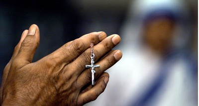 CHRISTIAN HOLDS A CRUCIFIX