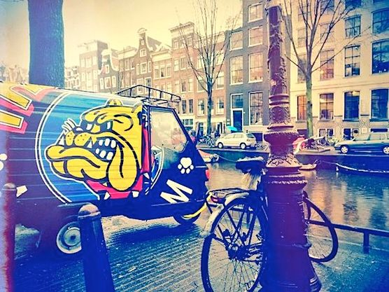 The company car of cafe bulldog the mack parked in front of a canal in Amsterdam.