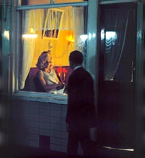 Amsterdam Red Light District in 1968. A man walks next to a brothel where a prostitute is waiting for customers.