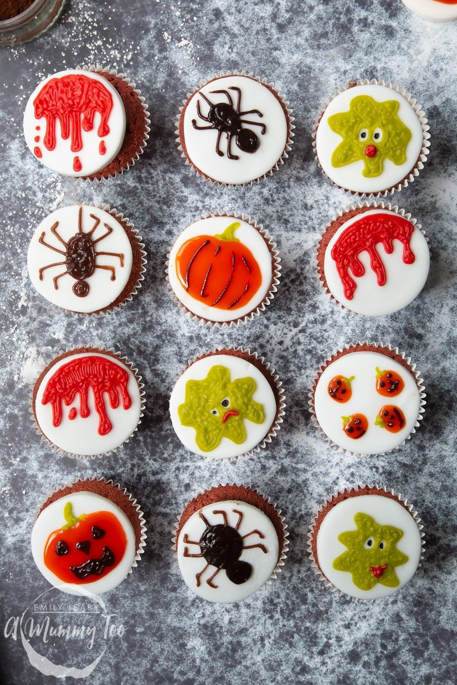 Dairy free Halloween cupcakes: red velvet cupcakes topped with chocolate frosting and white fondant discs decorated with icing pens. The designs include dripping blood, spiders, green monsters and pumpkins.