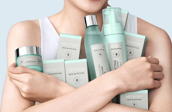 A person's arms are shown hugging the new Artistry Skin Nutrition collection to her chest.