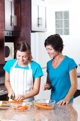 mother teaching teen daughter cooking