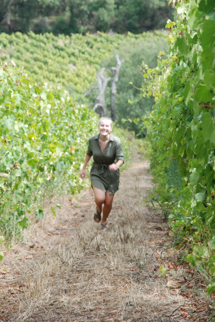 A girl running in the vineyards