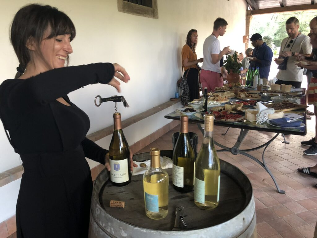 Opening a bottle of white wine. Tasting table with food and people