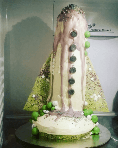 Birthday cake shaped like a tall rocket - cream with purple drippy icing and lime green fins with sparkling sprinkles.