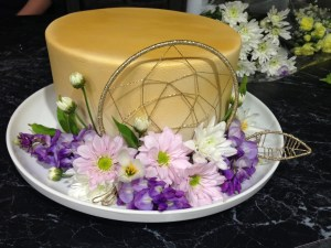 Front shot of cake, a single-tier 23cm round cake covered in fondant (with sharp corners!), sprayed gold, with a glittery gold dream catcher centered on the front side of the cake (it extends above the edge of the cake by about a centimetre); three sprays of purpley-blue wisteria are arranged around the bottom of the cake at the front on the white platter; they are filled out with three baby pink daisies, three white daisies, some white daisy buds, a few wisteria leaves, and a gold glittery feather or leaf made to match the dreamcatcher.