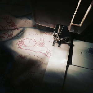 Close up of sewing machine foot in the process of stitching white or cream satin binding to a baby pink cotton fabric with a darker pink 'classic winnie-the-pooh' print on it. The scene is dark, lit only by the light of the sewing machine.
