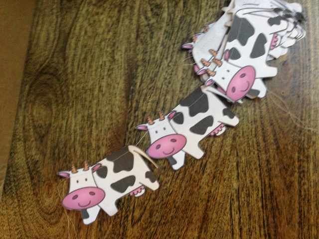 Garland of cute cartoony black-and-white cows strung together.