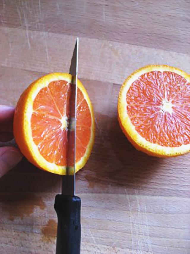 Knife slicing a half of an orange