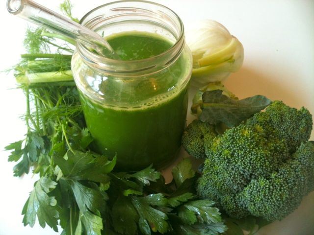 mason jar of green juice surrounded by greens, parsley and broccoli