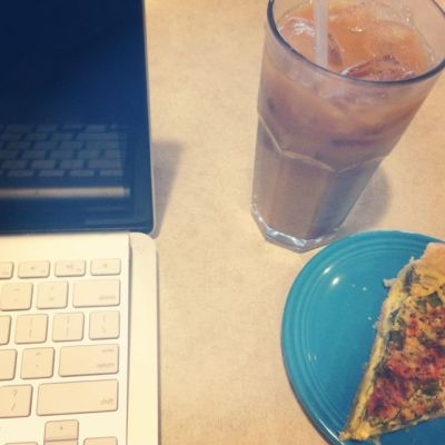 Computer and veggie quiche and iced almond milk vanilla toddy latte.