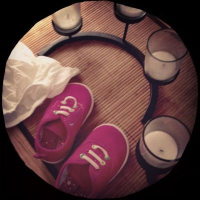 pink baby shoes sitting on a dresser