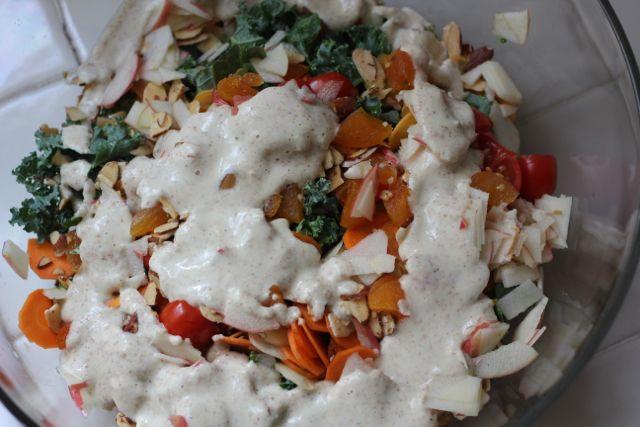 homemade dressing poured over kale salad